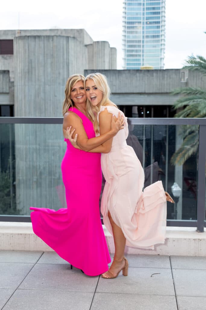 two women in pink dresses hugging and smiling at wedding reception in downtown orlando
