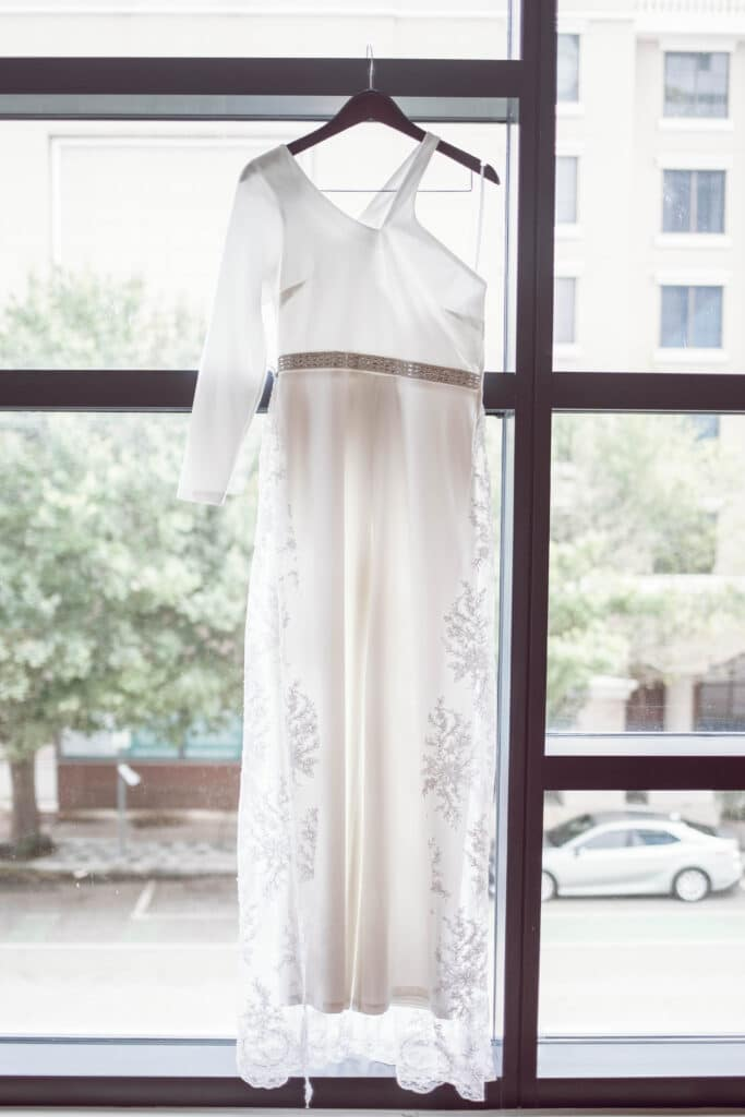 lace wedding dress on hanger hanging in front of large window