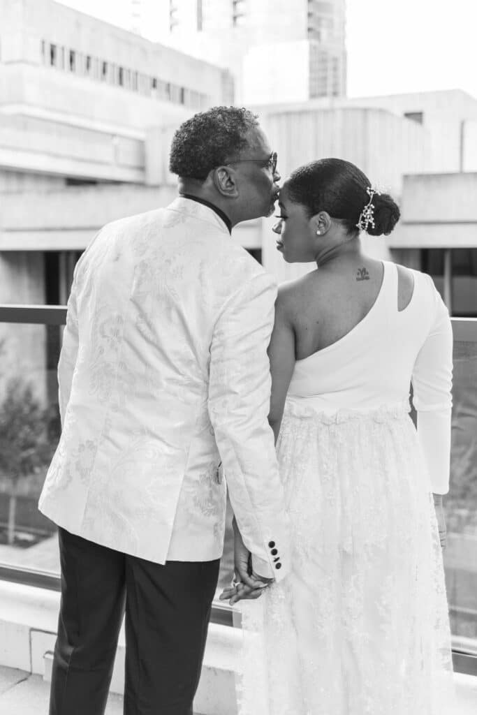 black and white photo of bride and groom holding hands and facing away from the camera
