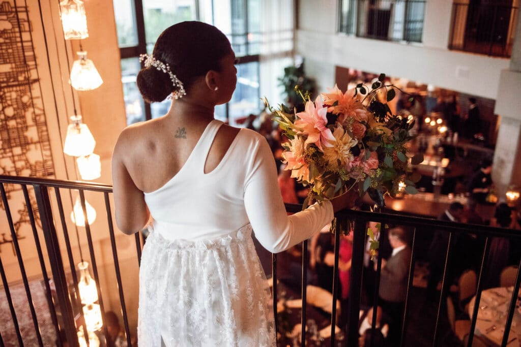 bride in single sleeve dress standing on balcony looking down into romantically lit reception area