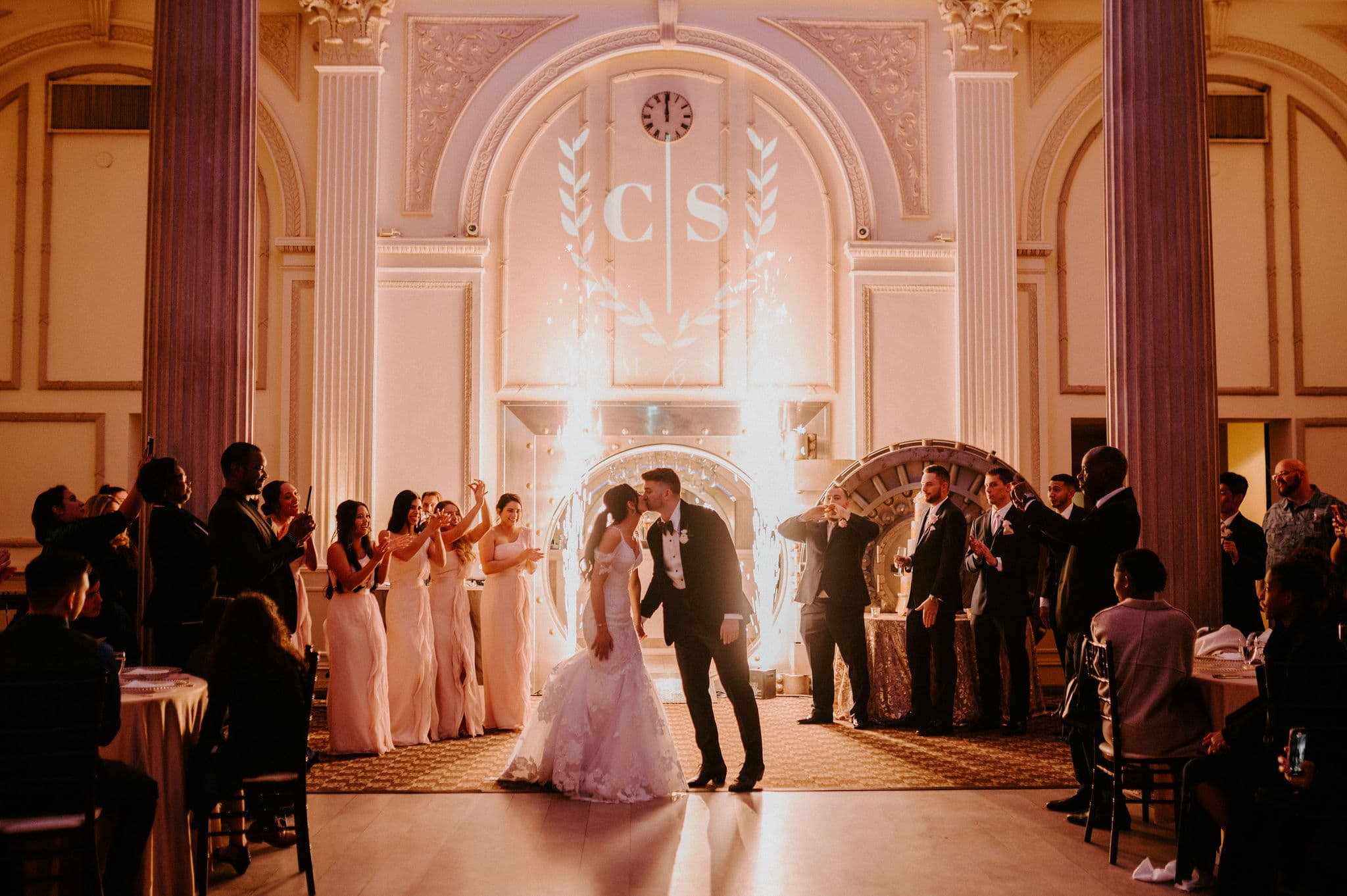 bride and groom entering their reception from a vault with wedding party clapping and cheering