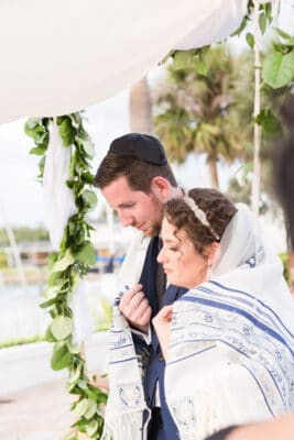 jewish couple wrapped in tallit in their modern jewish wedding ceremony