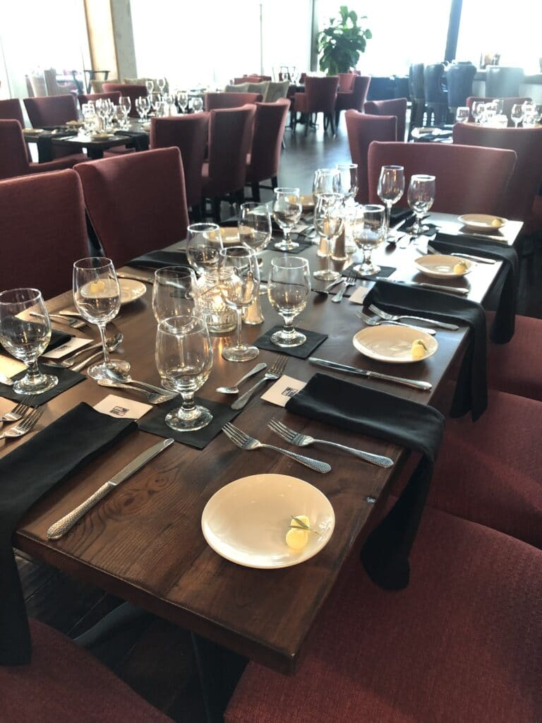 dark wood table with modern table settings and glassware and dark red chairs