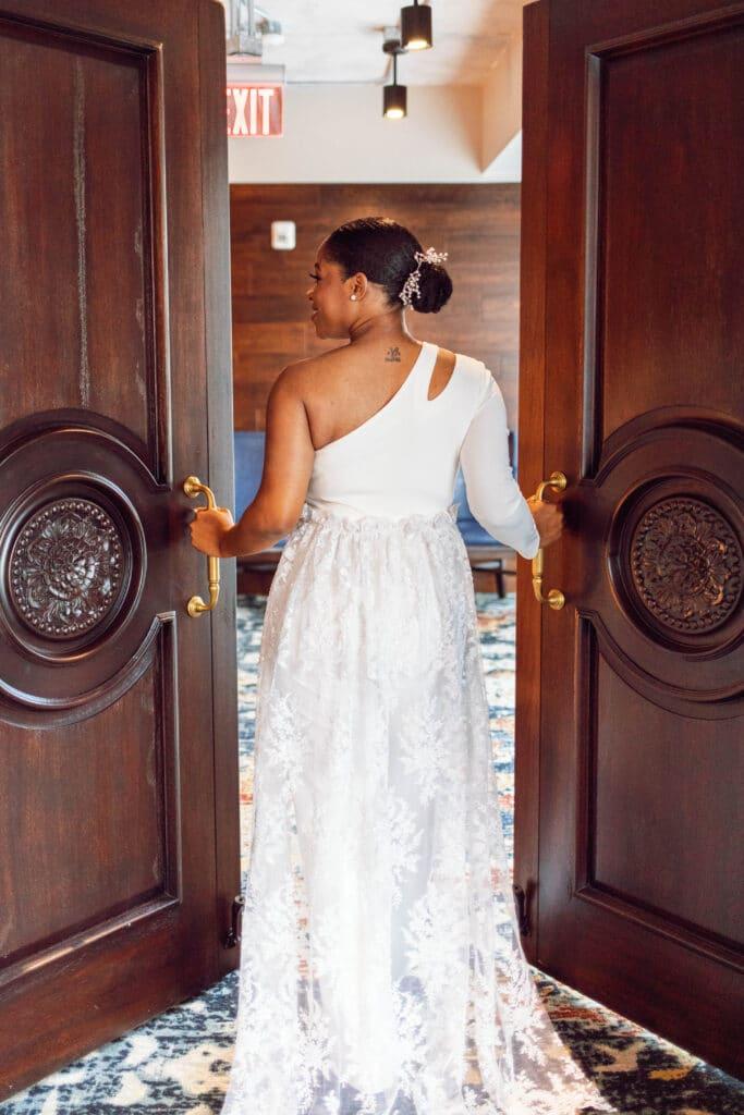 bride in single sleeve lace dress walking through large wooden doors