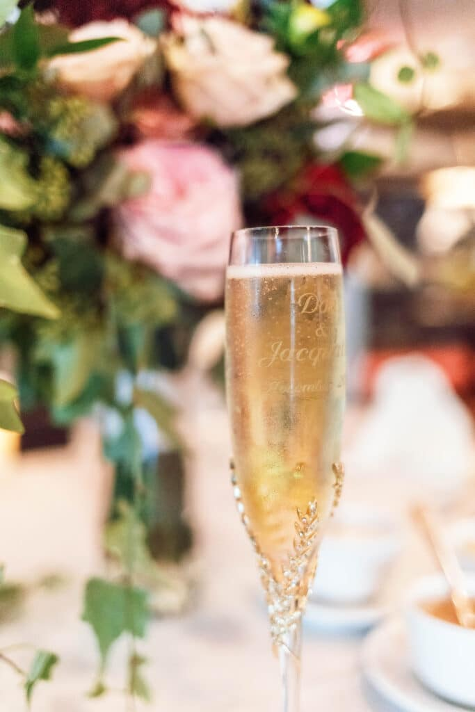 glass of champagne with pink and red flowers behind it