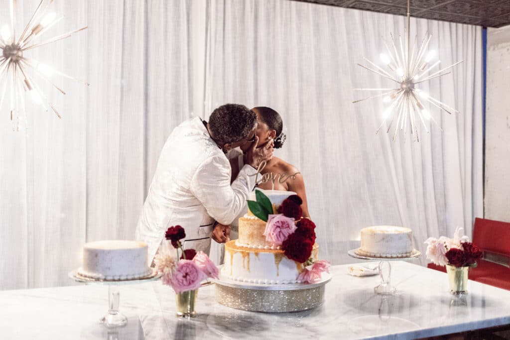 bride and groom kissing at cake table in front of white curtain with two modern chandeliers
