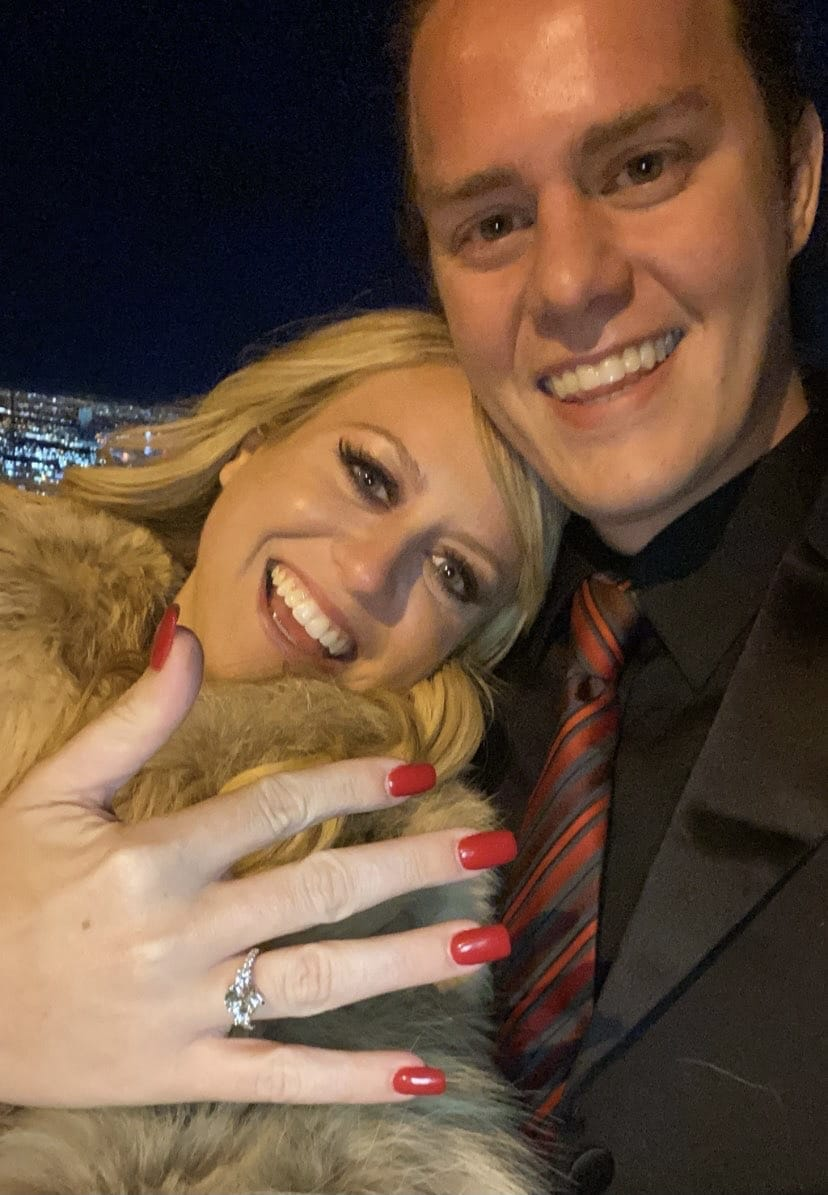 bride to be showing off her new engagement ring and groom to be smiling