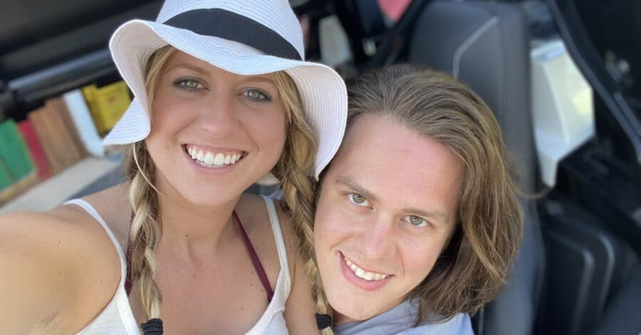 newly engaged couple sitting in golf cart and smiling together