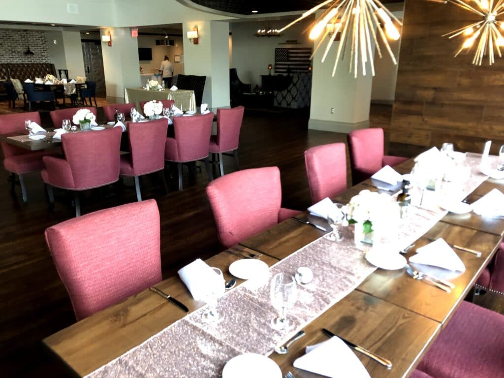 long wood table with white table settings and pink chairs