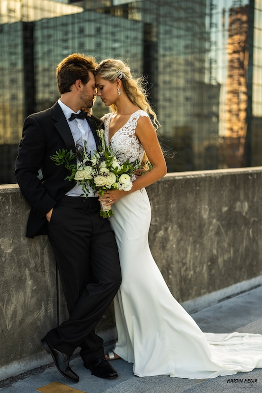 bride and groom embracing on top of downtown parking garage