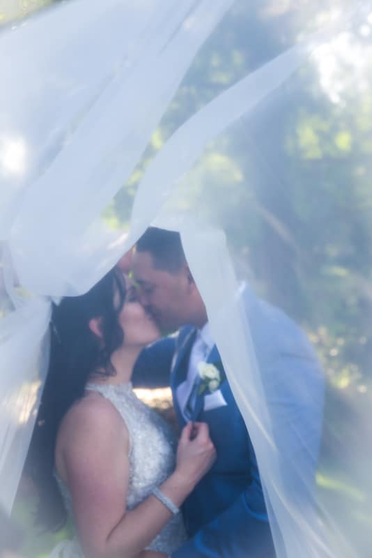 brides veil wrapped around bride and groom as they are kissing