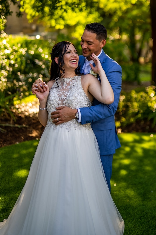bride laughing as her husband hugs her from behind