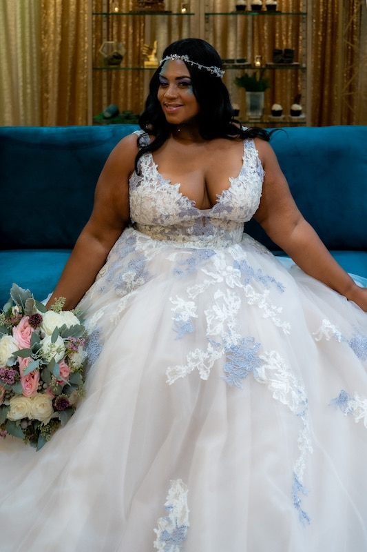 bride smiling while sitting on a blue couch that matches color accents on her dress