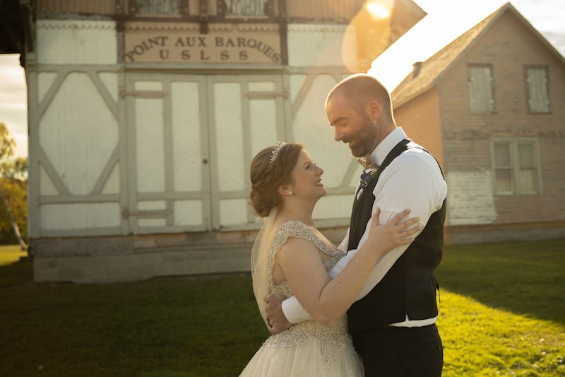 bride and groom embracing and smiling at each other while standing outside of rustic farmhouse buildings