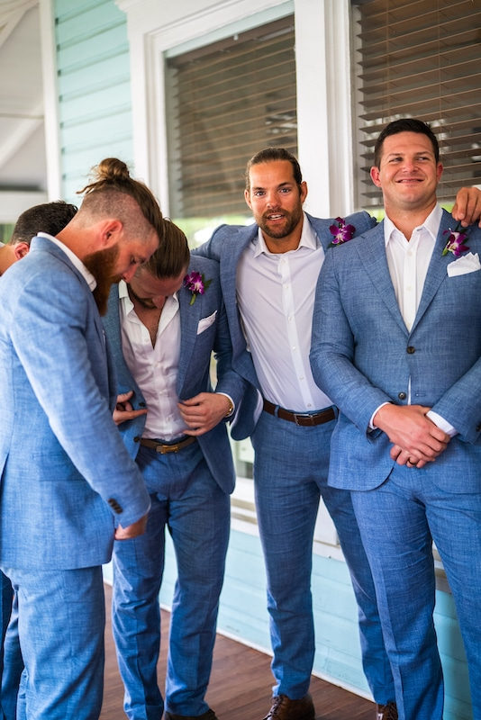 groomsmen in blue suits huddling before the wedding ceremony