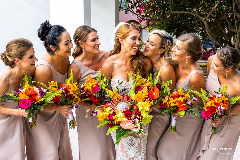 bride laughing with all of her bridesmaids