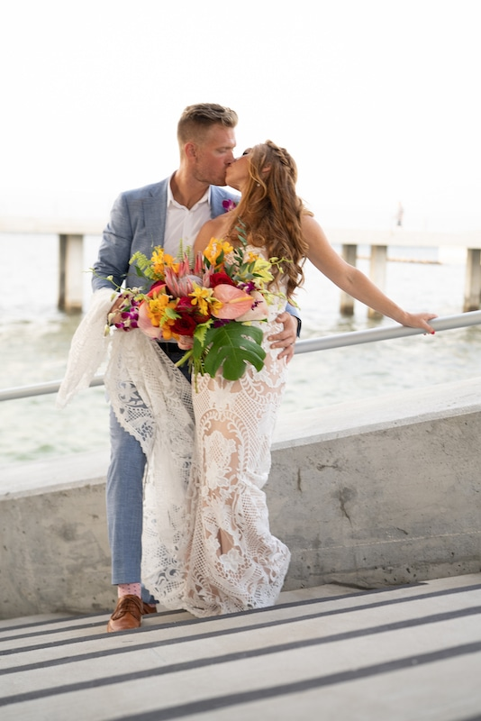 bride and groom kissing while leaning against railing of a boat ramp