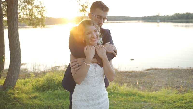 groom hugging his bride from behind while standing on shores of a large lake at sunset