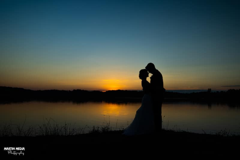 bride and groom embracing on shores of a lake, backlit by the setting sun