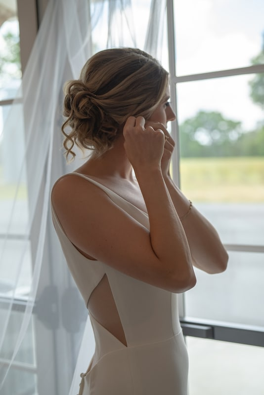 bride in wedding dress putting her earrings in while looking out the window
