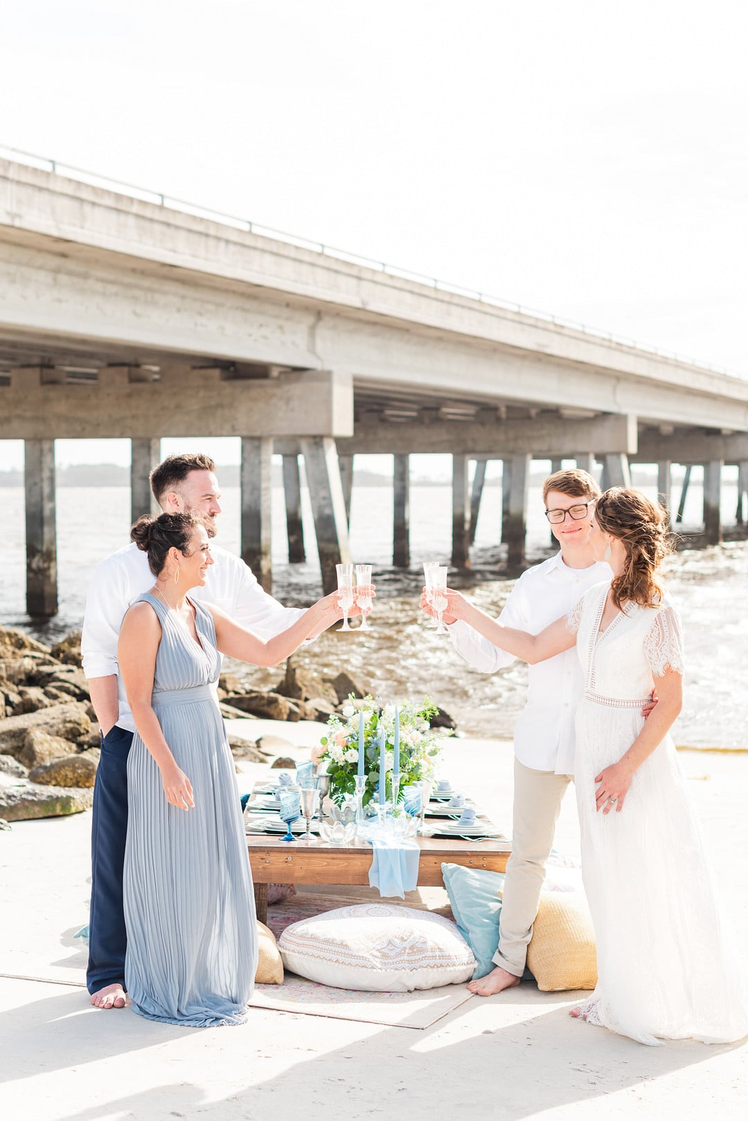 bride and groom toasting with their friends at the amelia island beach wedding inspiration shoot