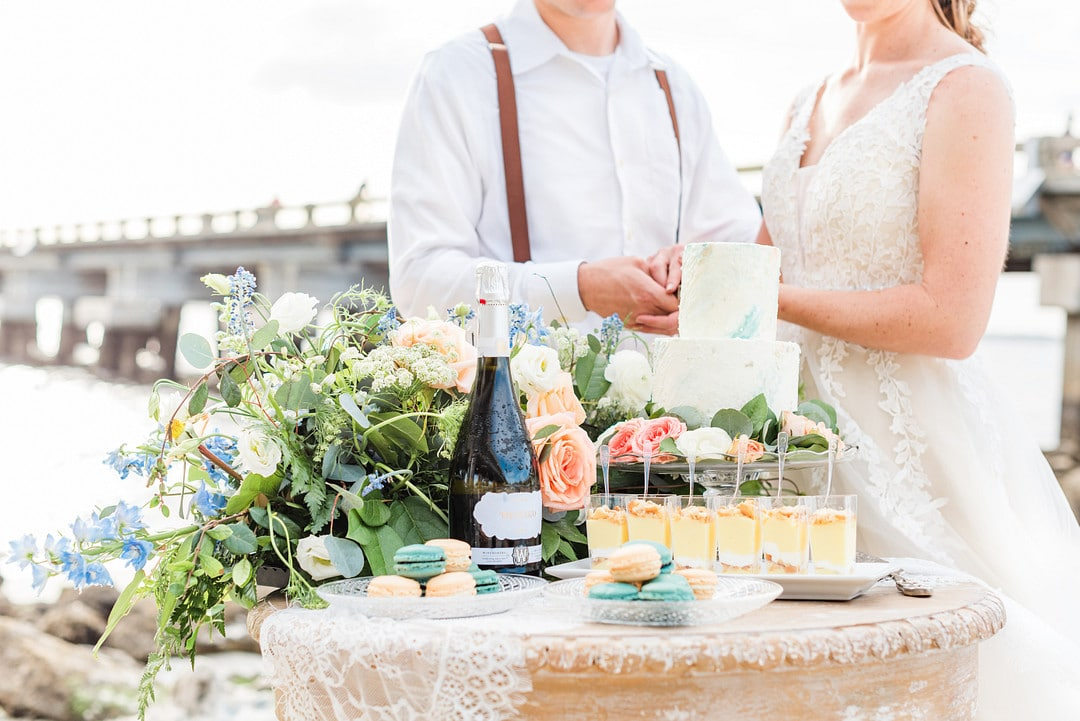 the dessert table with macrons, pudding, champagne and florals and the couple standing in the background