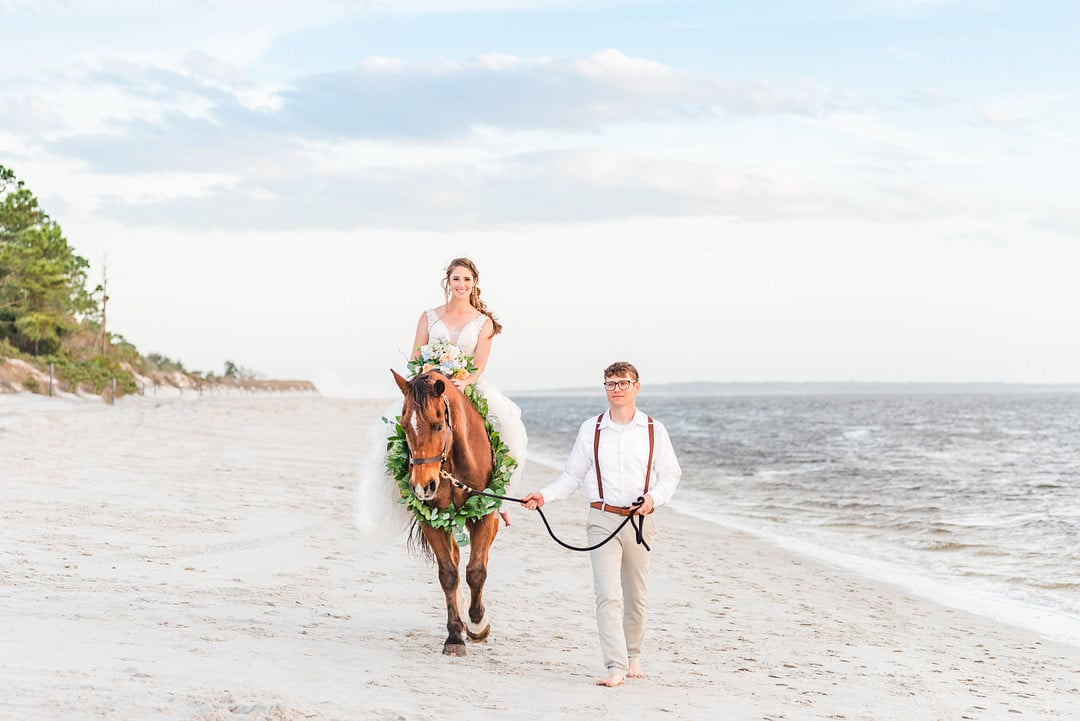 bride on a horse walking next to groom on amelia island