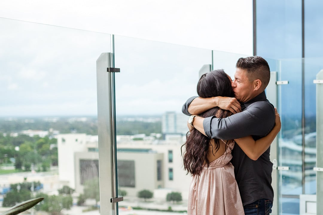 bride and groom to be hugging after proposal with views of the city behind them