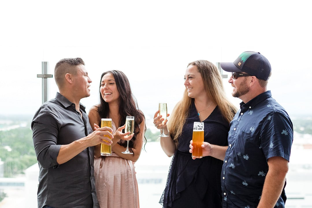 newly engaged couple having a drink with their friends after the aerial marriage proposal