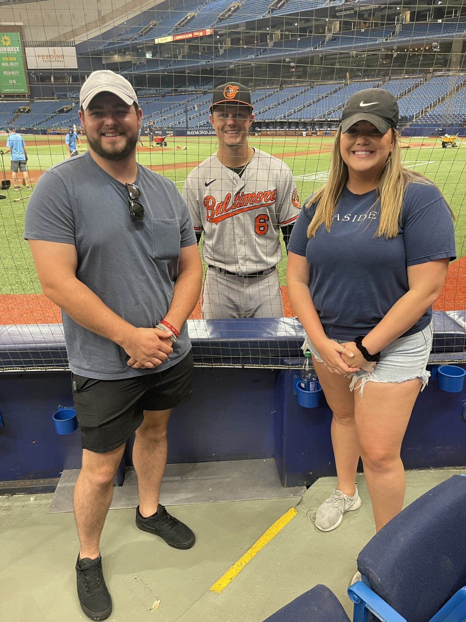 couple at a baseball game posing with one of the baseball players