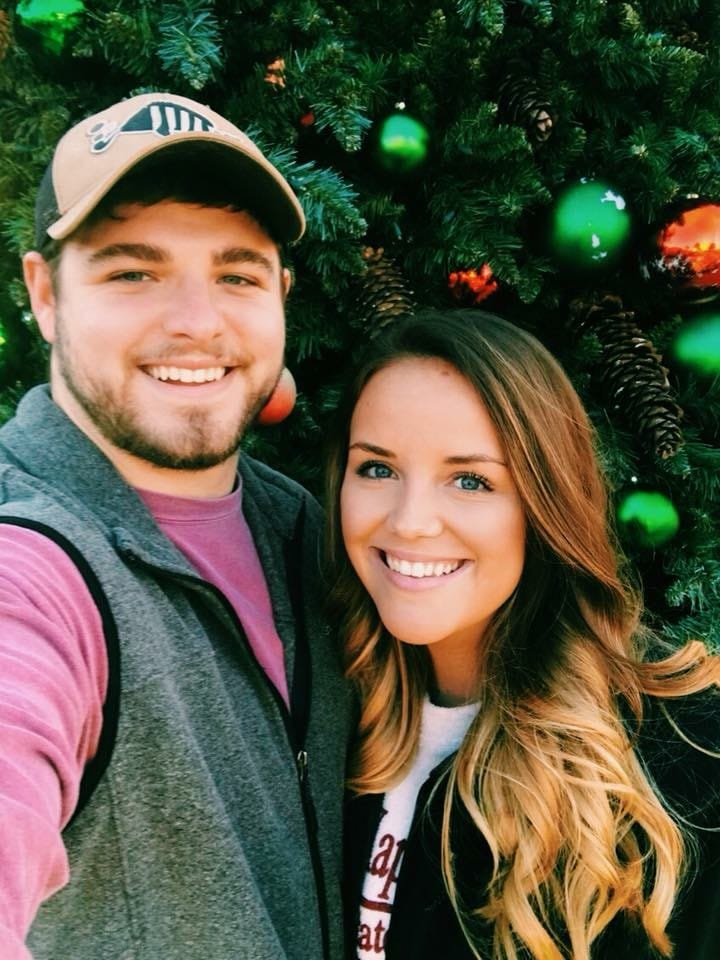 couple standing in front of a decorated christmas tree