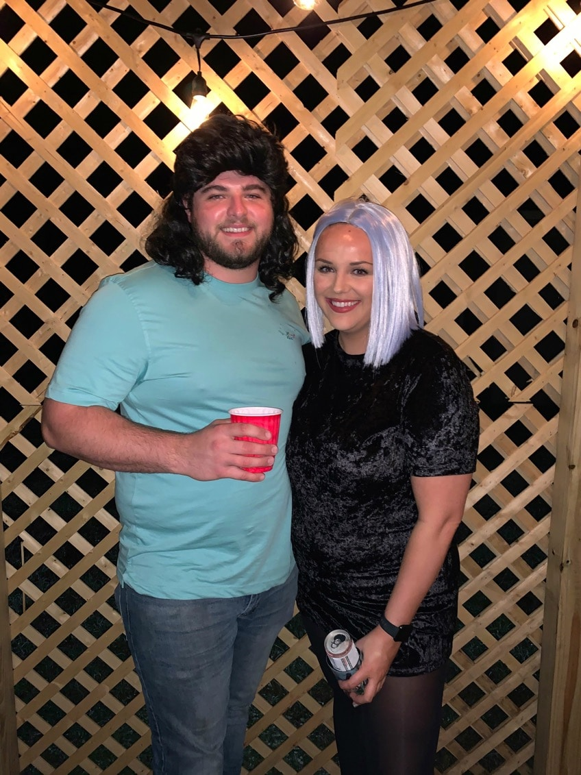 bride and groom to be wearing colorful wigs and drinks and smiling