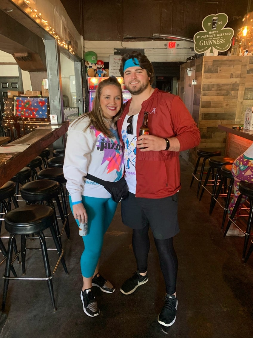 bride and groom to be dressed in 80s outfits holding drinks and smiling