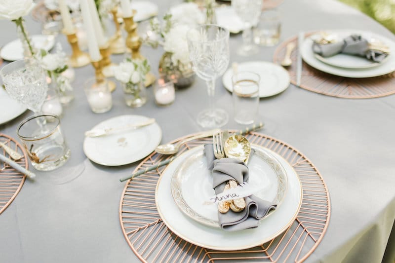 white plates with gold trim and matching gold silverware set up for wedding reception, rented from The Vintage Dish - Timely Tableware