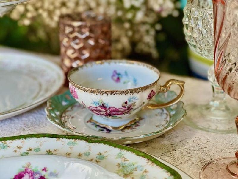 decorated tea cup in a saucer with gold trim and flowers painted on the cup