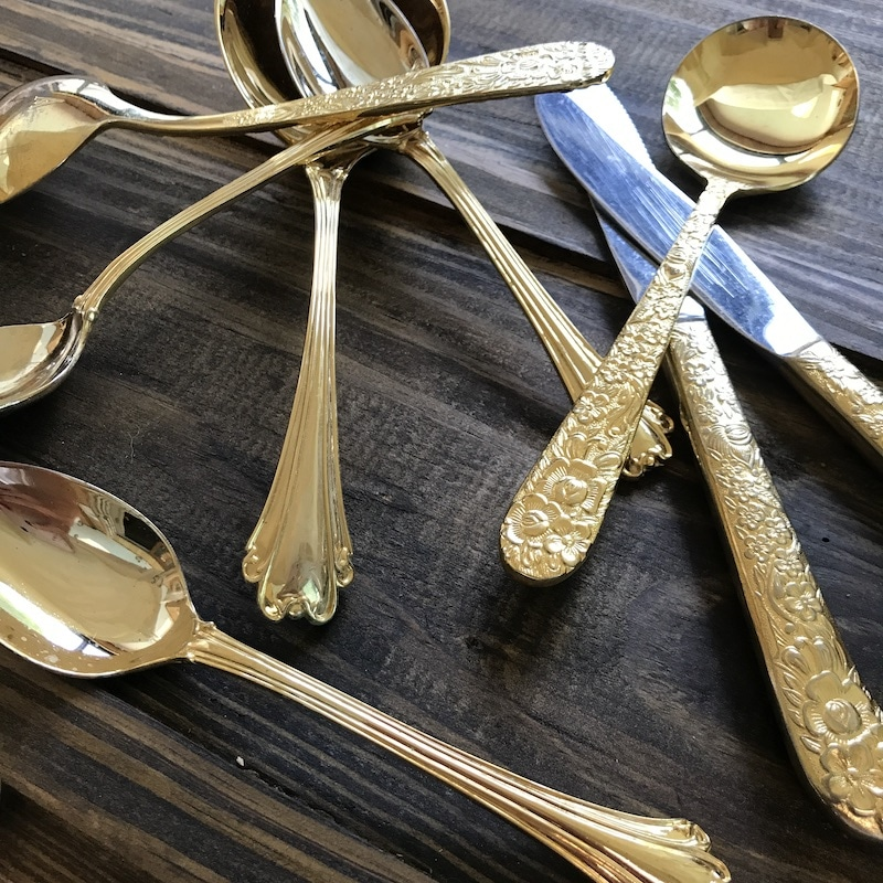 gold silverware displayed on a dark wood table