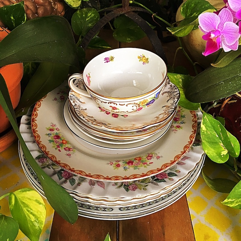 stack of dishes placed in between beautiful flowers