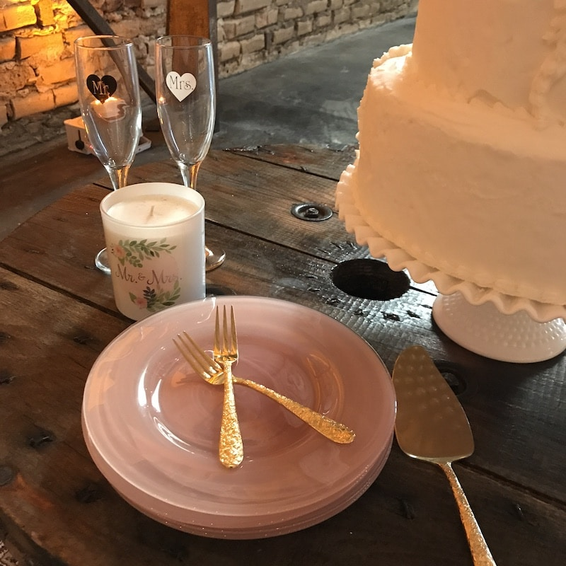 stack of pink plates and gold forks next to a white wedding cake