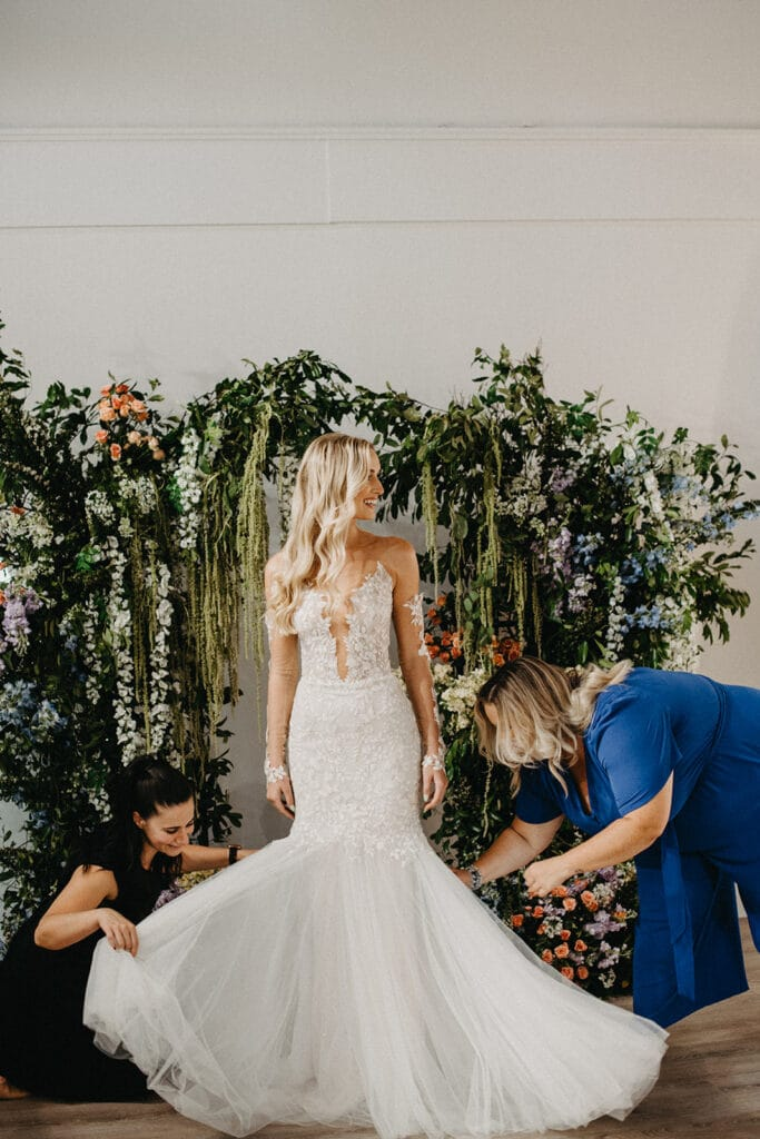bride smiling as women work on her dress
