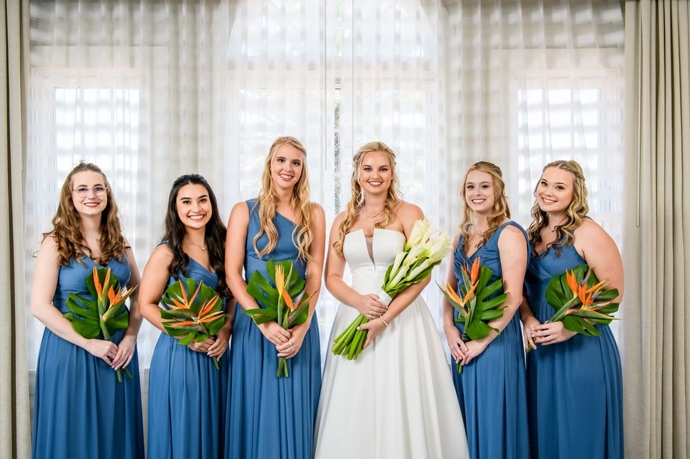 bride with bridesmaids in blue dresses holding tropical floral bouquets by jill heaton decor