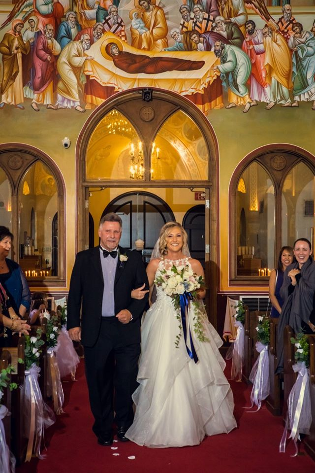 bride and groom walking down aisle after getting married in church with mural on ceiling