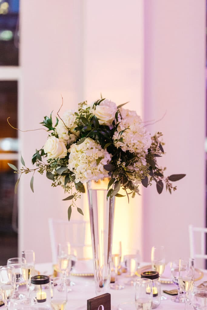 white floral arrangement in tall glass vase on white table