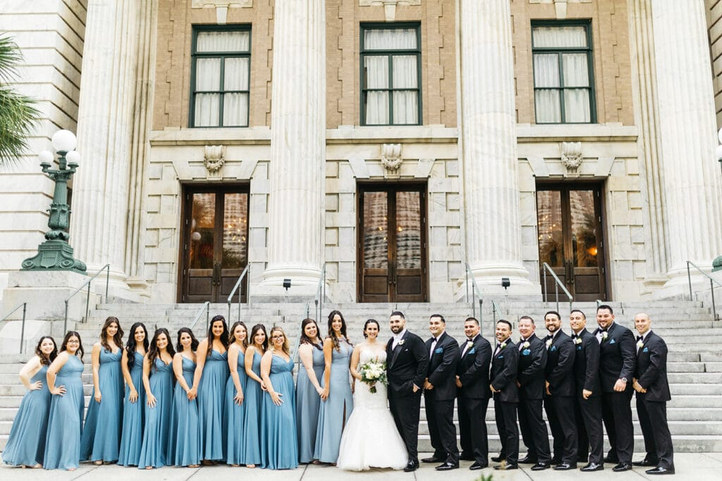 large bridal party in front of stone building