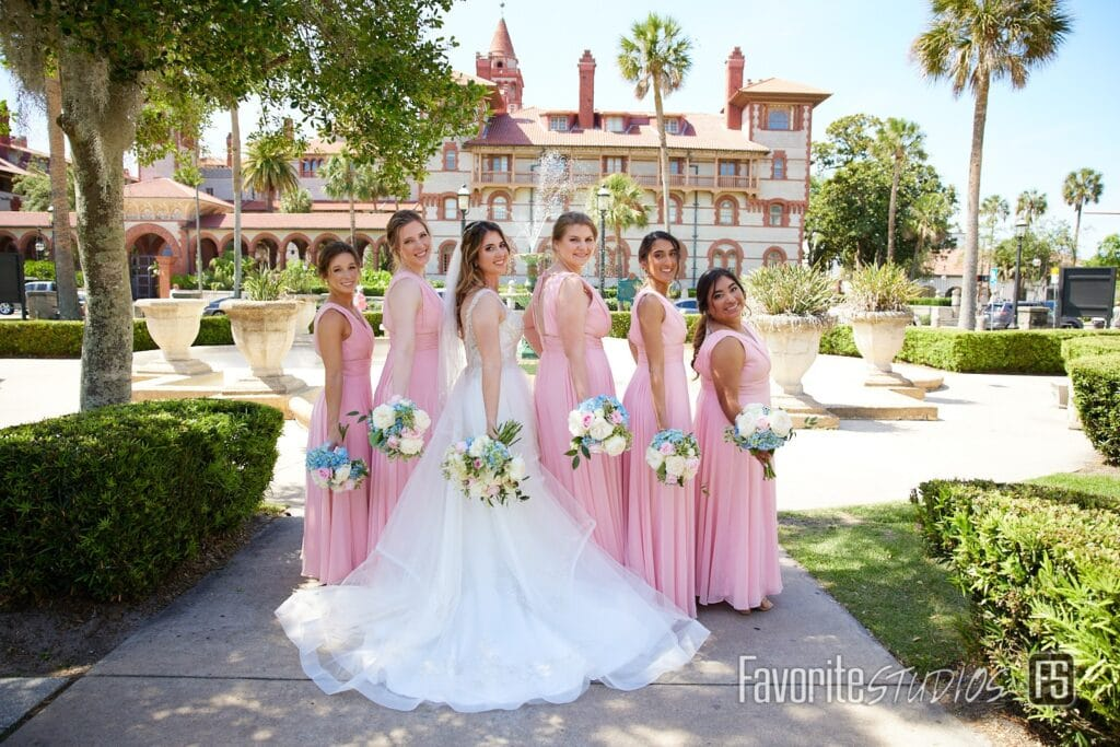 bride with bridesmaids in long pink dresses in front of spanish style building with palm trees