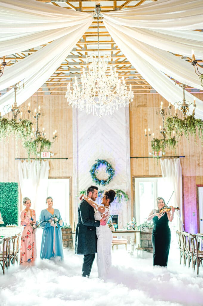 bride and groom enjoying first dance as bridesmaids watch and woman plays the violin
