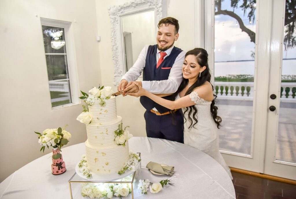 bride and groom cutting into cake with white flowers on each tier in ballroom facing lake