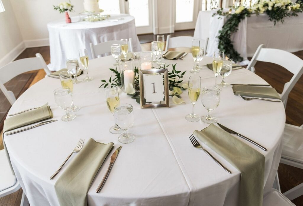 round table with white linens and small white floral centerpiece set up for wedding reception with table number 1 in frame