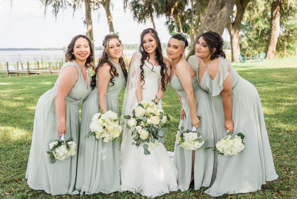 bride and four bridesmaids in light green dresses in front of lake with palm trees
