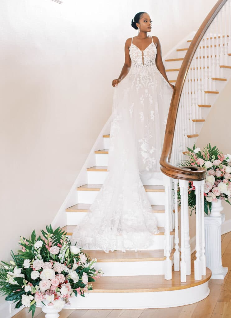 bride in dress with long lace train walking down wood staircase with large white and pink floral arrangements at the bottom