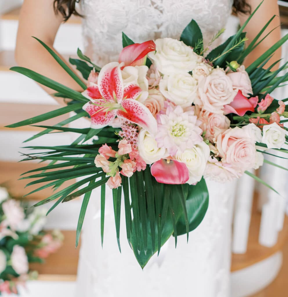 tropical wedding bouquet with bright pink flowers and large green leaves